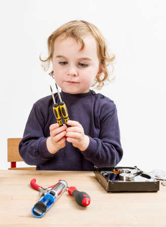collet: child choosing tool for repairing hard drive  Studio shot in gery background Stock Photo