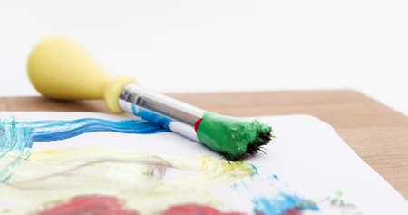 originating: green paint with paint brush  and paper on wooden table