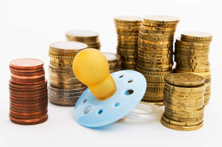 pacifier with hard money in background as symbol for the cost of parenthood Stock Photo