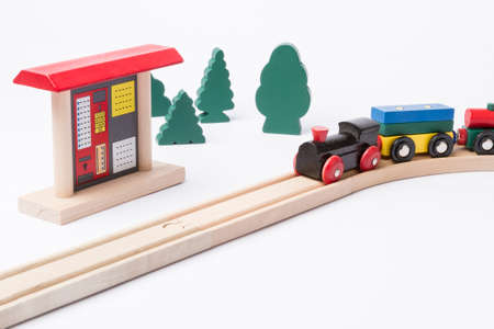 gewgaw: toy ticket machine at wooden railroad track with some trees