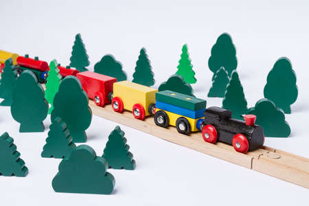 gewgaw: fast train driving through small forest  scenery made of wooden toy Stock Photo