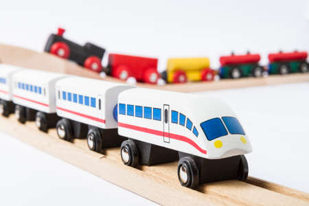 gewgaw: two wooden toy trains on railway isolated on white background