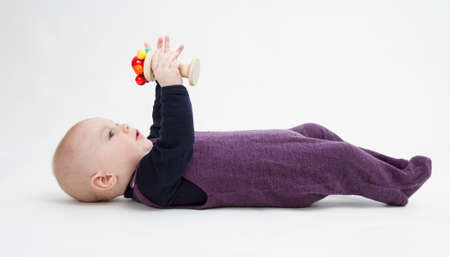 gewgaw: toddler lying on his back playing with wooden toy. grey background