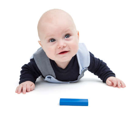 gewgaw: interested baby with toy block on floor isolated on white