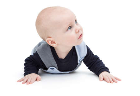 nursling: baby on flor in blue clothing looking to side Stock Photo