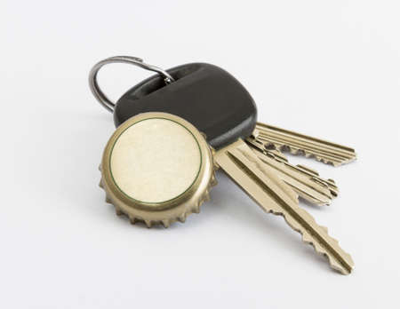 car key and bottle cap in close up with neutral grey background photo