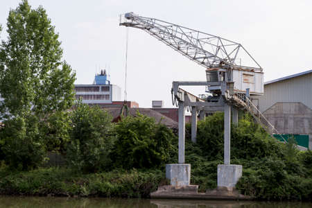 small, old dockside crane at river Neckar in germany Stock Photo