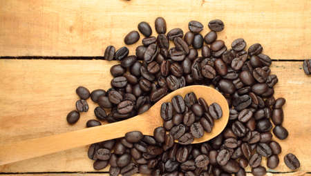 roasted coffee beans and  wooden spoon on table Stock Photo