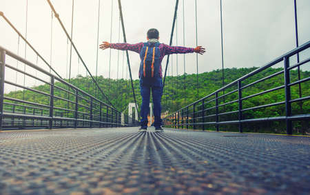 Freedom traveler man standing with raised arms,standing on bridge