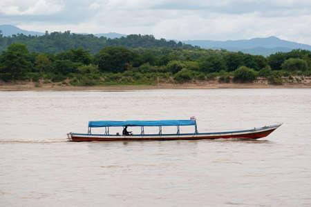 A man driving a long tail boat on the MEKHONG River Banco de Imagens