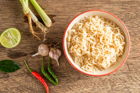 A cup of instant noodles placed on a wooden table With lime, chilli, lemon grass and garlic as ingredients, top view noodle Reklamní fotografie