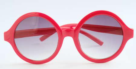 Gafas rojas sobre fondo blanco, objeto de cerca