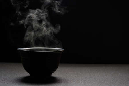 Soup hot in black bowl on wooden table,food steam and copy space ,selective focus.Fresh foods concept