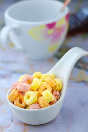 Cereal flakes in white spoon ceramic with copy space,Breakfast concept.Food with delicious fruity taste and fruity colours.Its made with maize,wheat,and barley