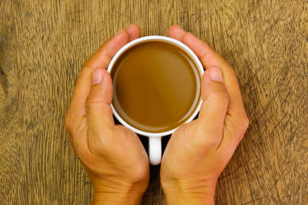 Close up  hand holding a cup of cocoa over wooden table, top view Stockfoto