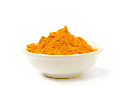 Turmeric powder in a bowl isolated white background.Close-up of powder orange color turmeric.