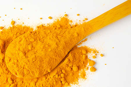 Dry turmeric powder and wooden spoon on  isolated white background.Close-up of powder orange color turmeric. Stockfoto