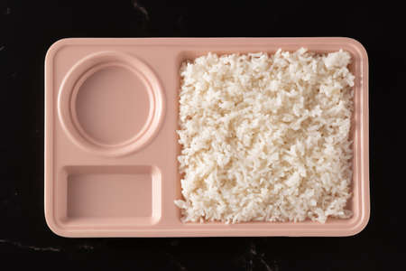 Rice in pastel bowls placed on a black background.There are two empty holes.top view food. 版權商用圖片