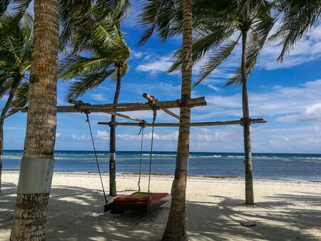 A hanging bed invites to relax in the shadows of the burning sun on Bohol