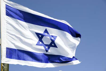 Israeli flag against the blue sky in the sun