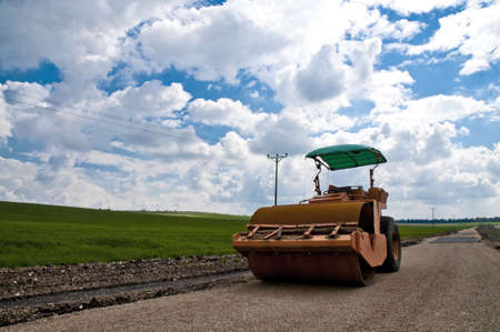 orange tractor on a background of grass and sky photo