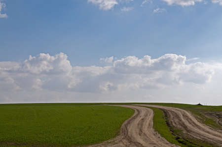 green field against blue sky with clouds Imagens