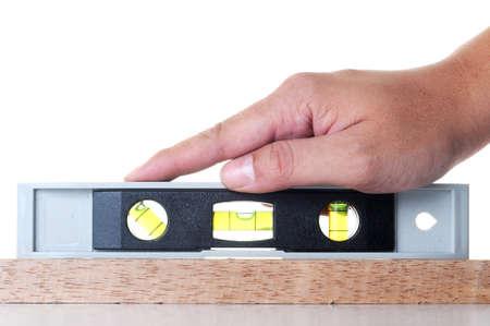 Een hand maatregel het evenwicht met meetinstrumenten op hout isoleren met witte achtergrond.
