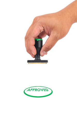 Hand hold approve Stamp in Green Color isolated white background photo