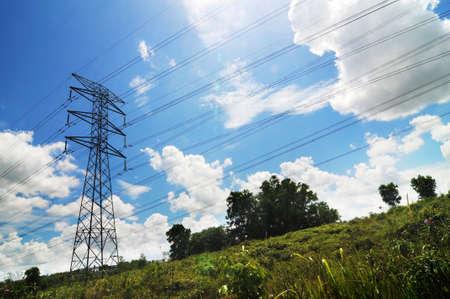 Hoogspanningsleidingen geïsoleerd met blauwe hemel achtergrond en groen voorgrond.