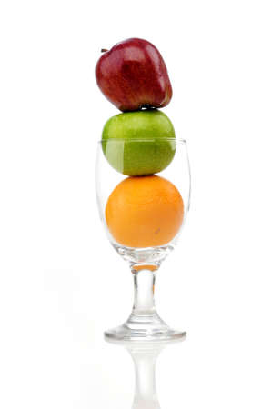 Mix of juicy fruits in wine glass isolated white background. The fruit sort in stack.