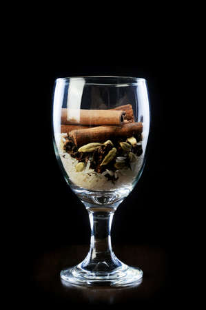 Star anise and rice with cinnamon sticks in wine glass isolaed black background photo