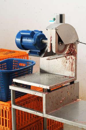 cutting machine is: Dirty chicken cutting machine with chicken box at the background