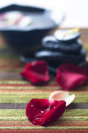 Drop of water on red flower petals isolated blur colorful petals, black rock and bowls photo