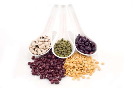 leguminosas: legumbres secas en tres cuchara blanco aislado fondo blanco