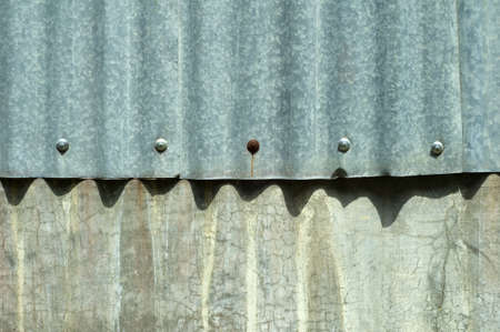 Old rust zink ovelaps concrete wall. There is rust nails. Stock Photo - 11124378