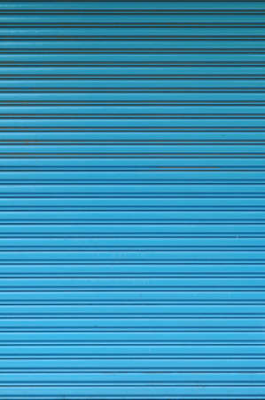 a blind: Pattern of blue roll up door. Close up of texture created by lines.