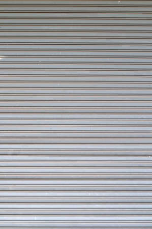 shutter door: Pattern of silver grey roll up door. Close up of texture created by lines. Stock Photo