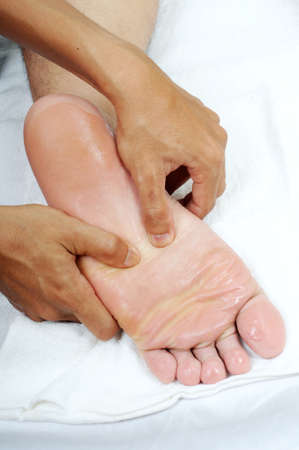 restore energy flow: reflexology foot massage with oil isolated whiite background