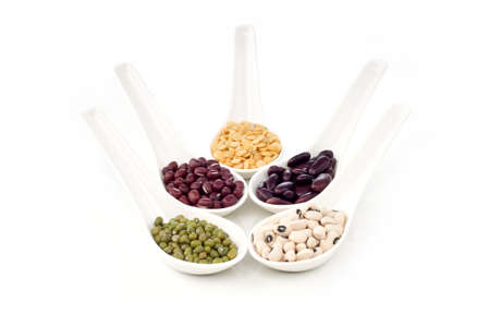 Various type of dry legumes on white spoon isolated white background