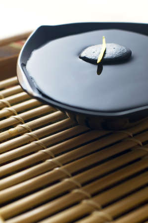 hot spring: Yellow flower petals on black rock in the middle of bowl full with water. The bowl on the empty bamboo tray. Stock Photo