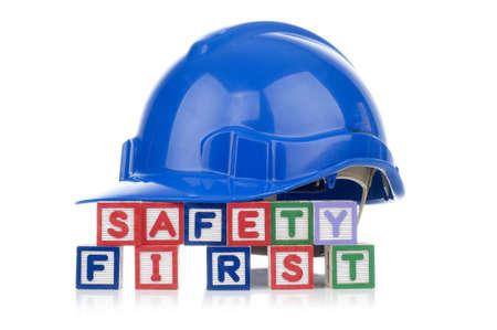 Alfabet blokken spelling Safety First met veiligheidshelm op het hoogste witte achtergrond
