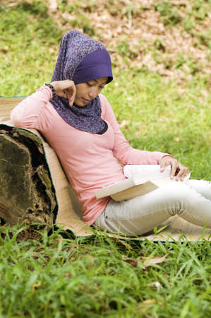 Beautiful young muslim lady lean again the tree stump reading isolated green grass and brown leaf photo
