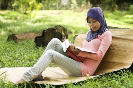Beautiful young muslim lady lean again the tree stump reading isolated green park photo