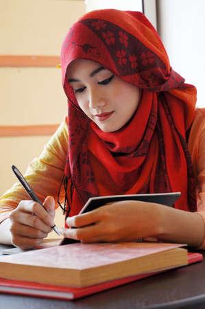 Mooie moslim vrouw met rode sjaal schrijven in een cafe