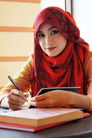 Beautiful muslim woman wearing red scarf holding pen looking to camera photo