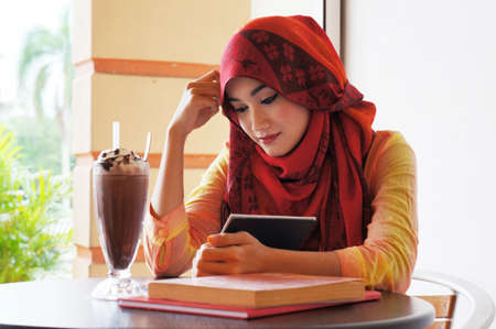 Beautiful muslim woman wearing red scarf  reading at a cafe with books and coffee on the table