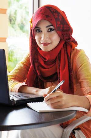 Mooie moslim vrouw met rode sjaal klaar om te schrijven in het cafe