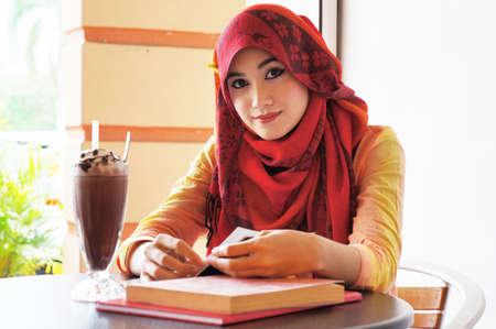 Mooie moslim vrouw met rode sjaal glimlach tijdens het lezen in het cafe