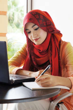 muslim woman: Beautiful muslim woman wearing red scarf writing beside a notebook at a cafe