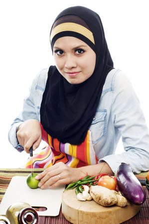 Beautiful muslim woman wearing scarf  cutting vagetables in the kitchen from upper view isolated white background Stockfoto